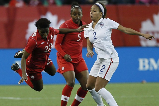 Kadeisha Buchanan (20) se fait faire un croc-en-jambe... (Photo John Woods, La Presse Canadienne)