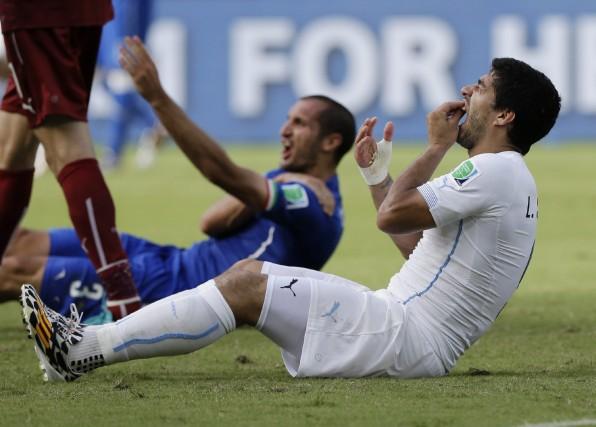 Luis Suarez porte sa main sur ses dents... (Photo archives AP)