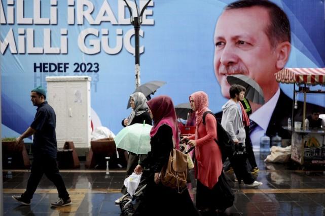 Des passants marchent devant une affiche électorale du... (PHOTO OZAN KOSE, AFP)