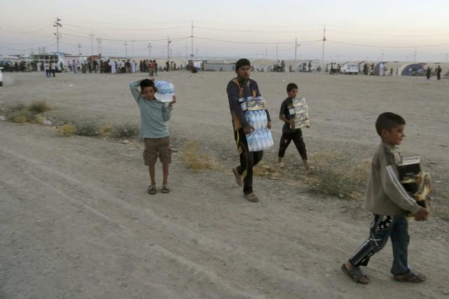 Des Irakiens de la minorités yazidie transportent de... (Photo Khalid Mohammed, AP)