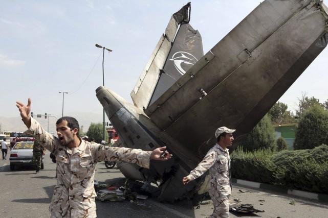 Les forces de sécurité iraniennes entourent les débris... (PHOTO ATTA KENARE, AFP)