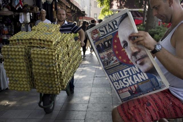 Un homme lit un journal oùRecep Tayyip Erdogan... (PHOTO EMILIO MORENATTI, AP)