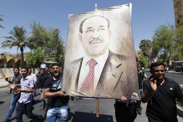 Des Irakiens transportent un portrait du premier ministre... (PHOTO AHMED SAAD, REUTERS)