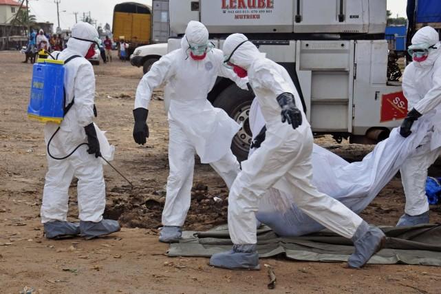 Des travailleurs humanitaires s'apprêtent à déplacer une victime... (Photo Abbas Dulleh, Associated Press)