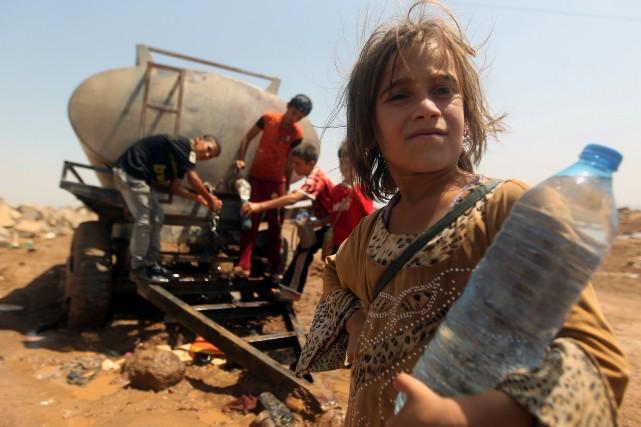 Une fillette yézidie s'abreuve près d'une citerne d'eau... (PHOTO AHMAD AL-RUBAYE, AFP)