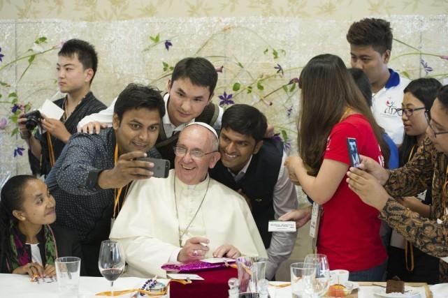 Le pape François pose pour des selfies avec... (PHOTO AGENCE FRANCE PRESSE)