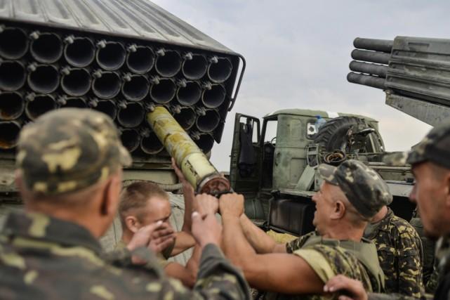 Des soldats chargent un système de lance-roquettes multiple... (PHOTO ALEKSEY CHERNYSHEV, AFP)