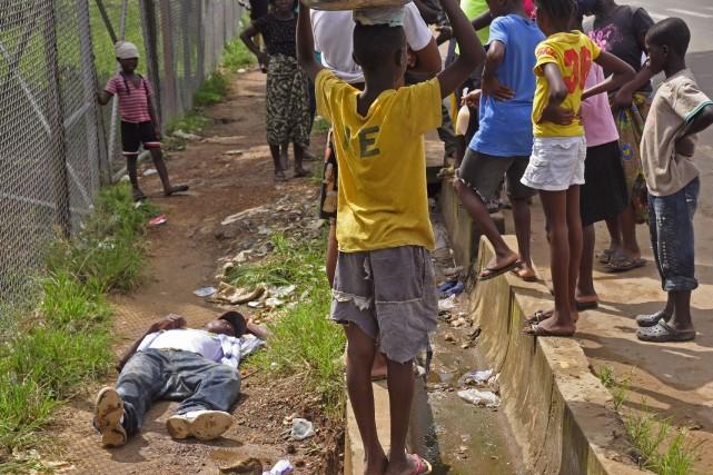 Des enfants se tiennent autour d'un homme soupçonné... (Photo Abbas Dulleh, AP)