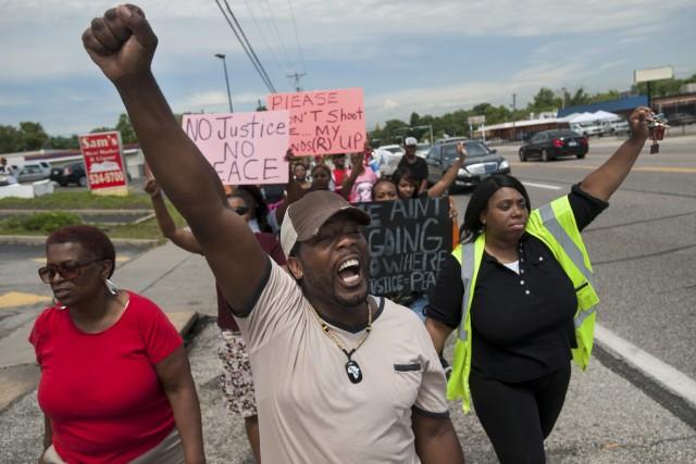 Des gens manifestent à Ferguson.... (PHOTO MARK KAUZLARICH, REUTERS)