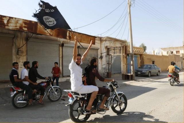 Un résidant de Tabqa agite le drapeau islamique... (PHOTO REUTERS)