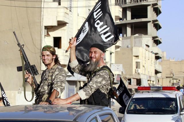 Des militants de l'EI, dont l'un agite un... (PHOTO ARCHIVES REUTERS/STRINGER)