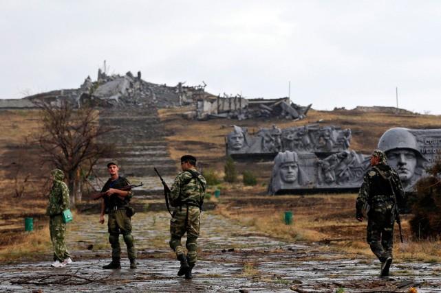 Des prorusses traversent un mémorial militaire, partiellement détruit,...