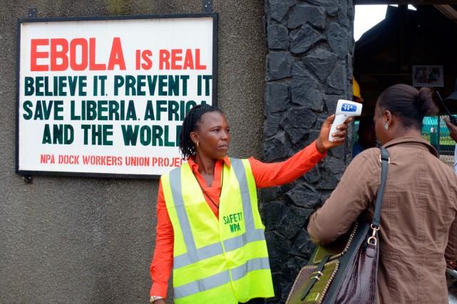 Un agent de sécurité prend la température d'une... (PHOTO DOMINIQUE FAGET, AGENCE FRANCE-PRESSE)