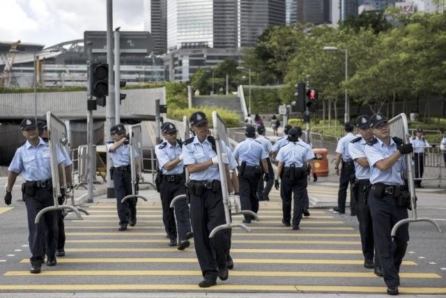 Des policiers transportent des barrières afin de protéger... (PHOTO ALEX OGLE, AP)
