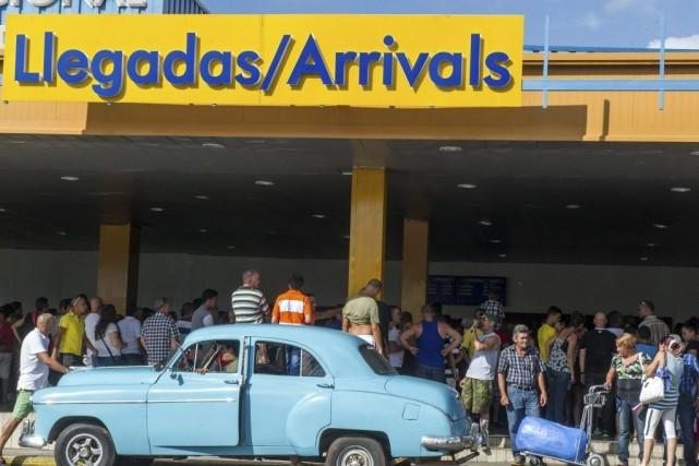 Des gens circulent à la sortie de l'aéroport... (PHOTO YAMIL LAGE, AFP)