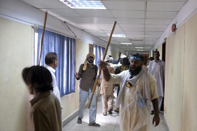 Des manifestants, munis de bâtons, ont détruit des... (PHOTO AAMIR QURESHI, AFP)