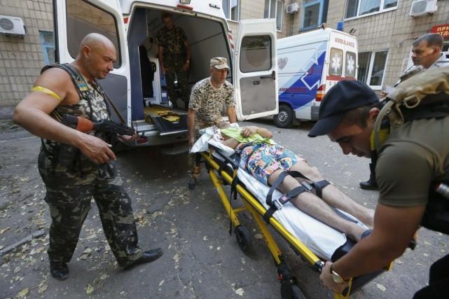 Un homme blessé s'apprête à être transporté dans... (PHOTO VASILY FEDOSENKO, REUTERS)