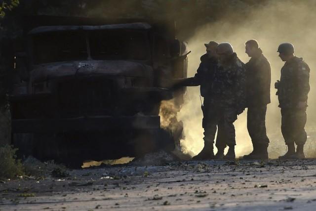 Des soldats ukrainiens examinent un véhicule de l'armée... (PHOTO PHILIPPE DESMAZES, AFP)