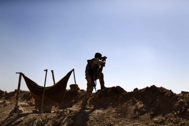 Un soldat kurde utilise des jumelles pour examiner... (PHOTO MARKO DROBNJAKOVIC, AP)