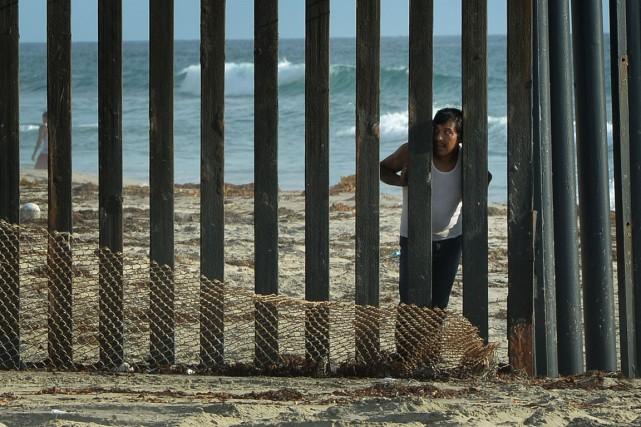 Un homme regarde à travers la clôture qui... (PHOTO MARK RALSTON, ARCHIVES AFP)