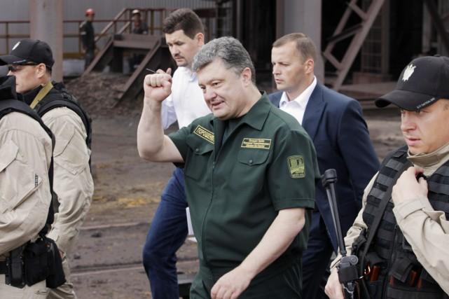 Le président ukrainien Petro Porochenko salue des travailleurs... (PHOTO VASILY FEDOSENKO, REUTERS)