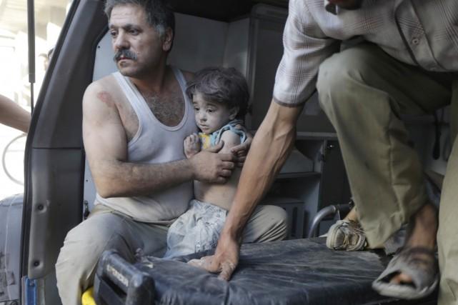 Un homme tient dans ses bras un enfant... (PHOTO BASSAM KHABIEH, REUTERS)