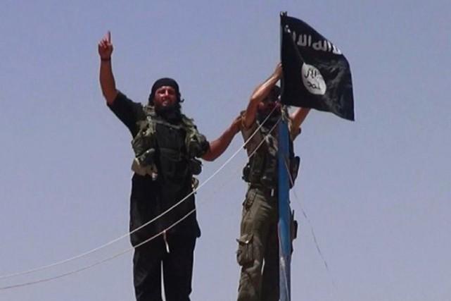 Des militants de l'État Islamique installent leur drapeau... (PHOTO ARCHIVES AFP)