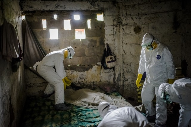 Une équipe spécialisée procède à l'enlèvement du corps... (Photo Daniel Berehulak, The New York Times)