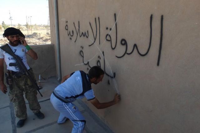 Un homme irakien gribouilleun X par-dessus un graffiti...
