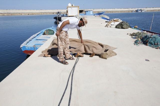 Un employé de la Garde côtière libyenne inspecte... (PHOTO ISMAIL ZITOUNY, REUTERS)