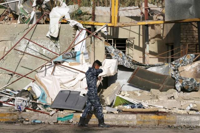 Un policier fédéral irakien inspecte les lieux d'un... (PHOTO KARIM KADIM, AP)