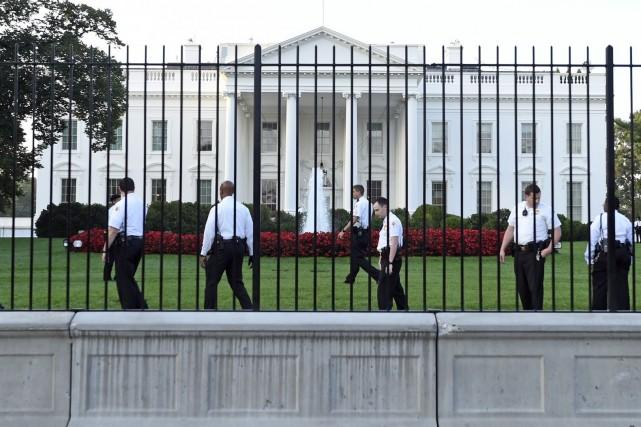 Des policiers scrutent le terrain de la Maison-Blanche... (PHOTO SUSAN WALSH, AP)