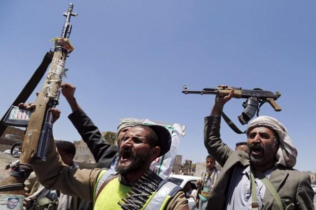 Des rebelles chiites brandissent leurs armes à un... (PHOTO KHALED ABDULLAH, REUTERS)