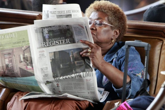 Une femme lit le Los Angeles Register.... (Photo: AP)