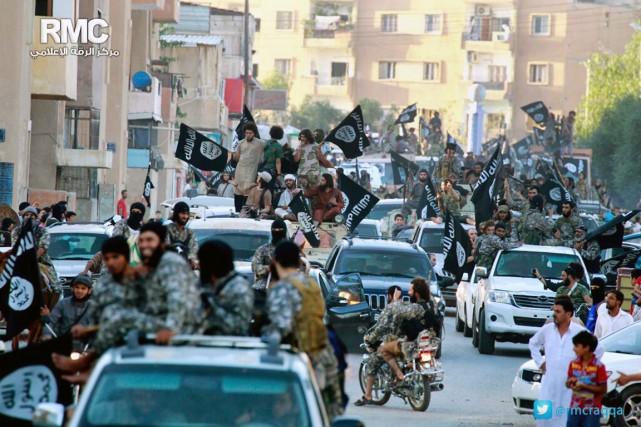 Des combattants du groupe État islamique paradent dans... (PHOTO ARCHIVES AP)