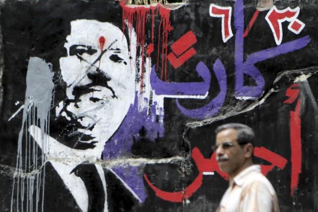 Depuis la destitution de M.Morsi (graffiti ci-dessus), des... (PHOTO AMR ABDALLAH DALSH, ARCHIVES REUTERS)