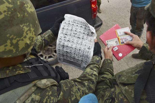 Des soldats inspectent un véhicule et contrôlent ses... (PHOTO YURI CORTEZ, ARCHIVES AFP)