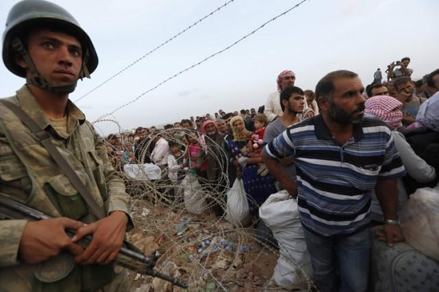 Un soldat turc surveille des réfugiés kurdes syriens... (Photo: Reuters)