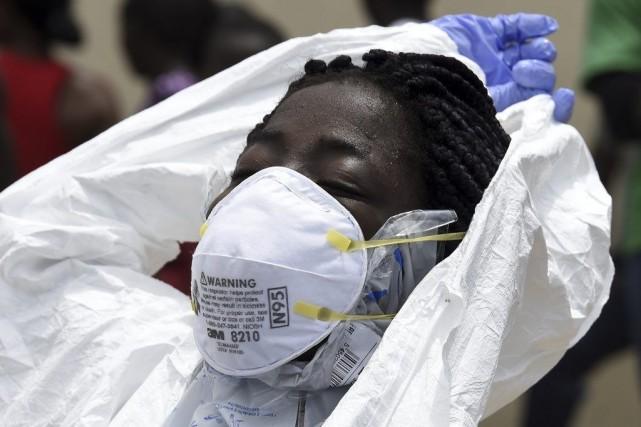Une travailleuse de la Croix-Rouge retire ses vêtements... (PHOTO PASCAL GUYOT, AFP)