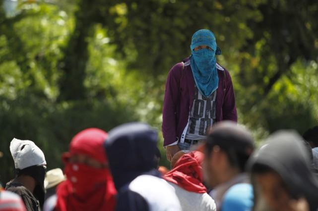 Des étudiants masqués ont marché dimanche en soutien... (Photo: Reuters)