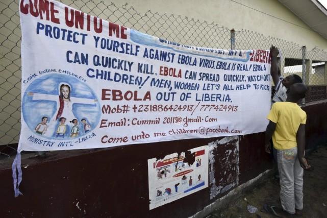 Des travailleurs de l'UNICEF installent une bannière dans... (PHOTO PASCAL GUYOT, AFP)