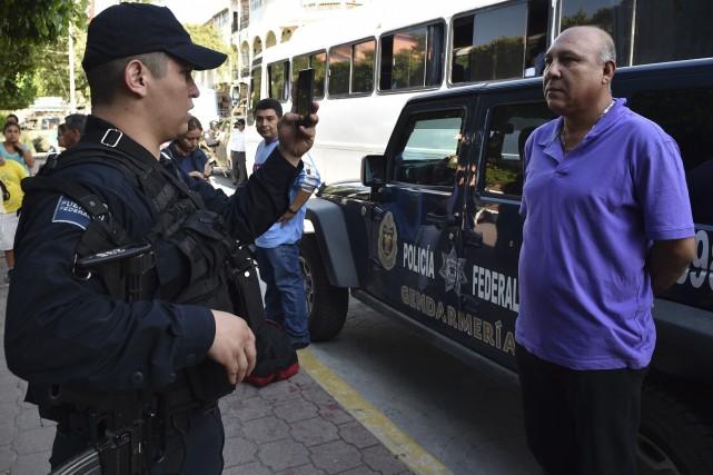 Un policier des forces spéciales prend une photo... (PHOTO Yuri CORTEZ, AFP)