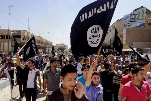 Des partsians de l'EI défilent dans les rues... (PHOTO ARCHIVES AP)