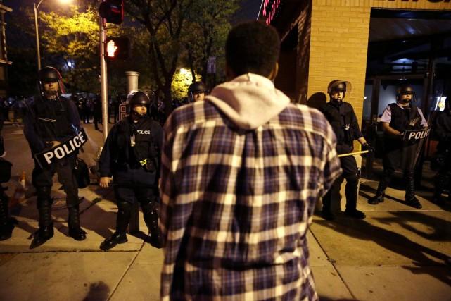 Un manifestant fait face aux policiers anti-émeute, à... (PHOTO JEFF ROBERSON, AP)