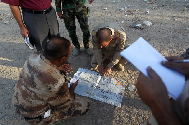 Des officiers de l'armée irakienne regardent une carte... (PHOTO AHMAD AL-RUBAYE, AFP)