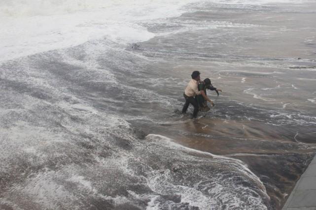 Un homme transporte sa femme après qu'une vague... (PHOTO REUTERS)