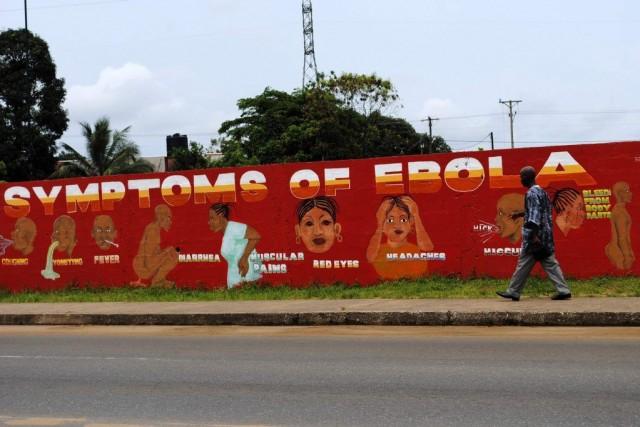 Un homme passe devant une murale indiquant les... (STRINGER)