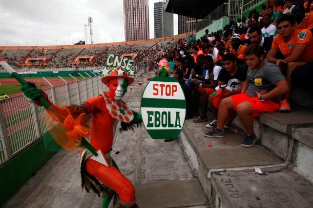Un spectateur brandit une affiche «Stop Ebola» lors... (Photo Luc Gnago, Reuters)