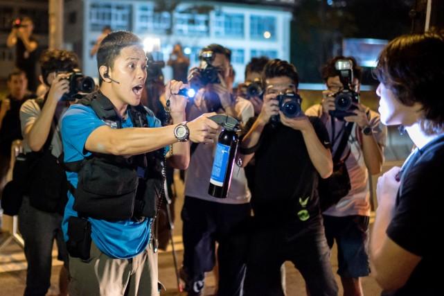 Un policier armé d'un vaporisateur au poivre menace... (PHOTO ALEX OGLE, AFP)