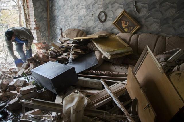 Un homme ramasse les débris accumulés dans sa... (PHOTO DMITRY LOVETSKY, AP)